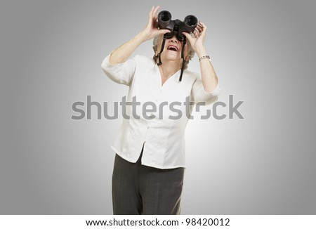 portrait of a senior woman looking through binoculars against a grey background - stock photo