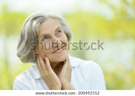 Portrait of a senior woman on a walk in the park in late spring