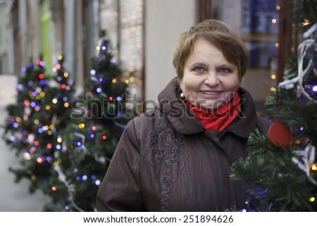 Portrait of a senior woman over vivid winter lights. Focus on woman's face. - stock photo
