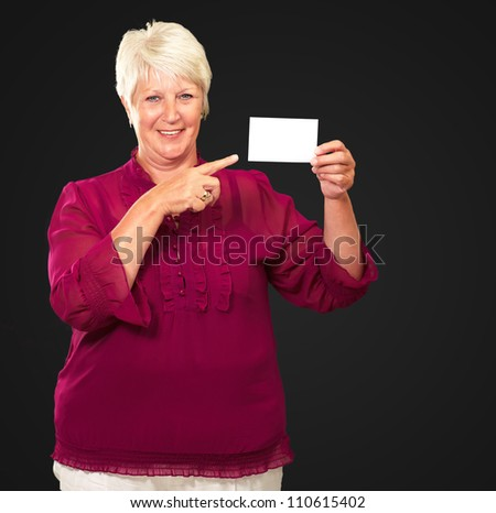 Portrait Of A Senior Woman Pointing To The Blank Card On Black Background
