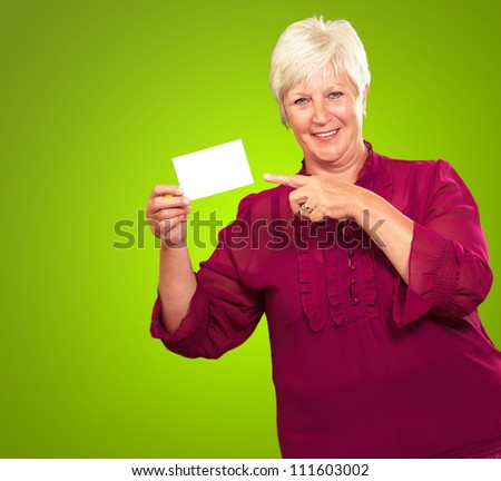 Portrait Of A Senior Woman Pointing To The Blank Card On Green Background - stock photo