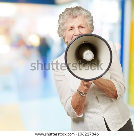 portrait of a senior woman screaming with a megaphone at a crowded place - stock photo