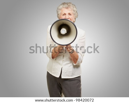 portrait of a senior woman screaming with a megaphone over a grey background - stock photo
