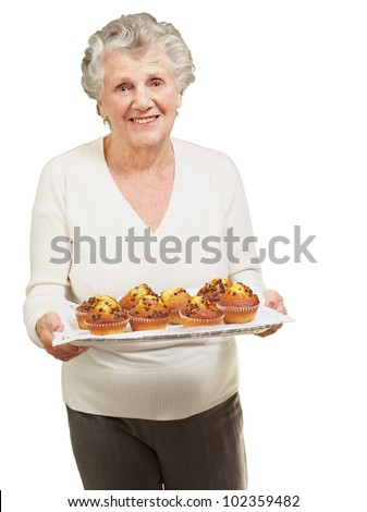 portrait of a senior woman showing homemade muffins over a white background - stock photo