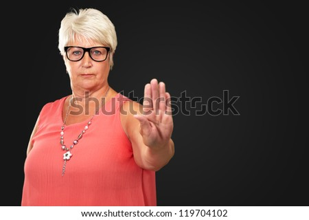 portrait of a senior woman showing stop sign on black background - stock photo