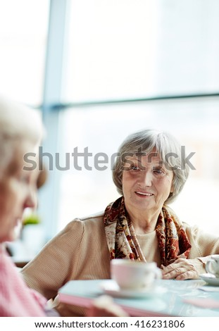 Portrait of a senior woman sitting at cafe - stock photo
