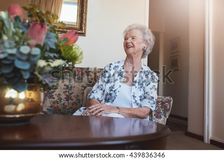 Portrait of a senior woman sitting on a sofa at old age home looking away and smiling. - stock photo