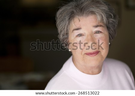 Portrait Of A Senior Woman Smiling At The Camera - stock photo