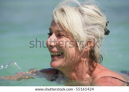 Portrait of a senior woman smiling bathing in the sea - stock photo