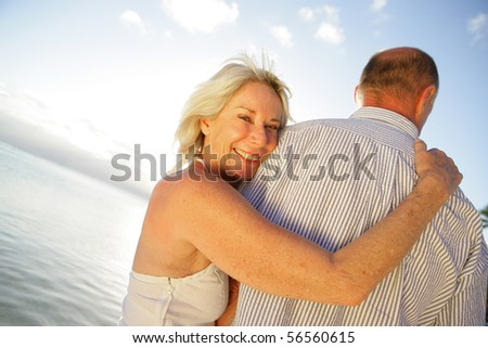 Portrait of a senior woman smiling embracing a senior man at the seaside - stock photo