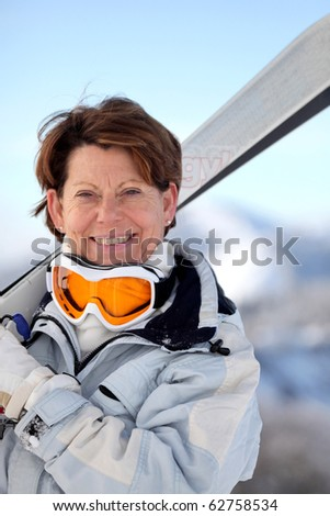Portrait of a senior woman smiling in snow - stock photo