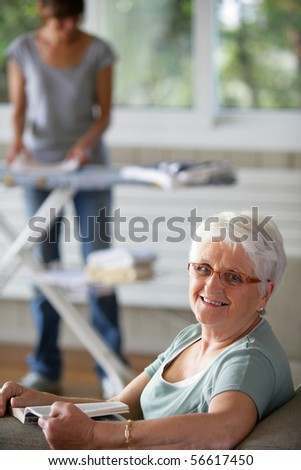 Portrait of a senior woman smiling on a sofa in front of a young woman folding laundry - stock photo