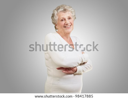 portrait of a senior woman smiling over a grey background