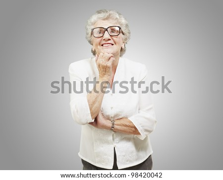 portrait of a senior woman thinking and looking up over a grey background - stock photo