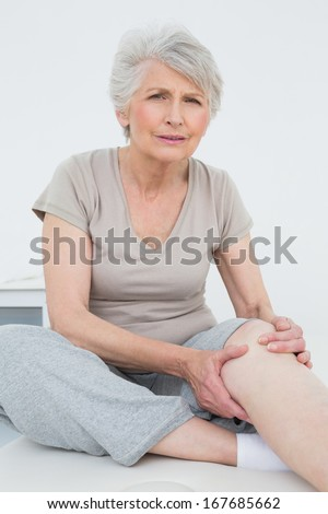 Portrait of a senior woman with a painful knee sitting on examination table - stock photo
