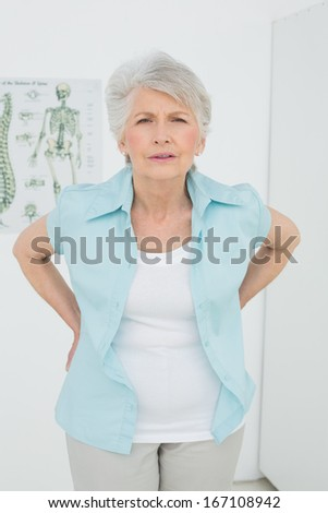 Portrait of a senior woman with back pain standing in the medical office - stock photo