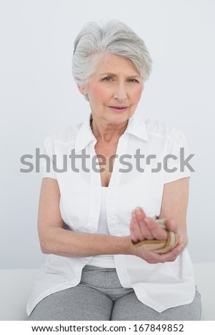 Portrait of a senior woman with hand in wrist brace sitting in the medical office - stock photo