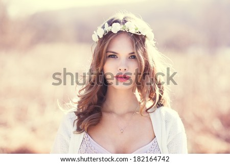 portrait of a sensual blonde with flowers on her head. photo done in the spring on a sunny day field - stock photo
