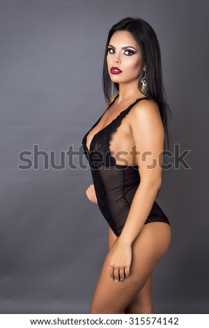 Portrait of a sensual brunette woman posing in sexy black lingerie over gray background - stock photo
