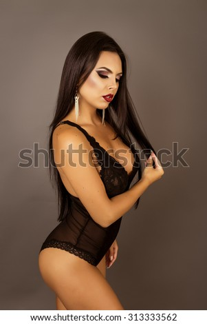 Portrait of a sensual brunette woman posing in sexy black lingerie.Studio shot - stock photo