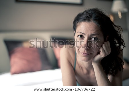 Portrait of a sensual woman lying on bed in hotel room. Shallow depth of field. - stock photo