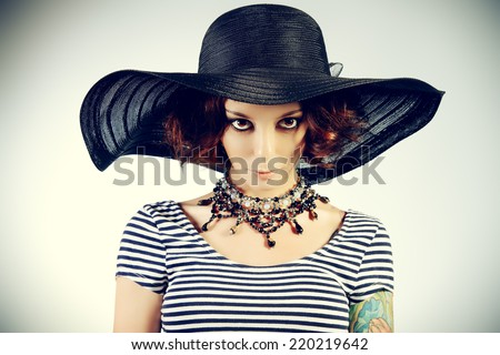 Portrait of a sensual young woman in a slinki dress and hat with a wide brim. Beauty, fashion. - stock photo