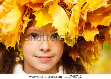 Portrait of a serene girl with a yellow autumn headwreath - stock photo