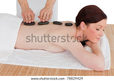 Portrait of a serene red-haired woman posing while receiving a massage in a spa centre