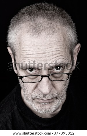 Portrait of a serious adult man wearing glasses with an inquisitive look.