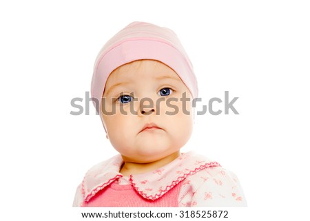 Portrait of a serious baby in a pink hat on a white background