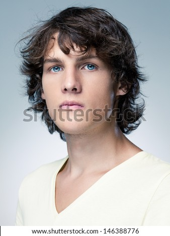 Portrait of a serious blue-eyed young man in front of a blue background. - stock photo