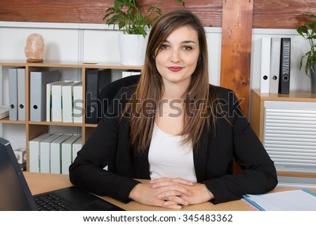 Portrait of a serious business woman at work in a bright office - stock photo