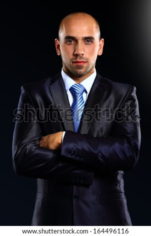 Portrait of a serious businessman on black background - stock photo
