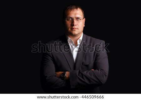 Portrait of a serious businessman on dark background