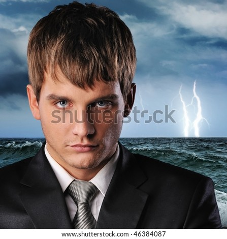 Portrait of a serious businessman over dark stormy sky - stock photo