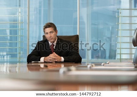 Portrait of a serious businessman sitting at conference table - stock photo
