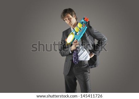 Portrait of a serious businessman standing with water gun against gray background - stock photo