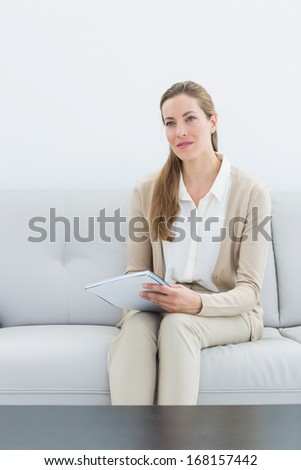 Portrait of a serious female financial adviser sitting on sofa at home