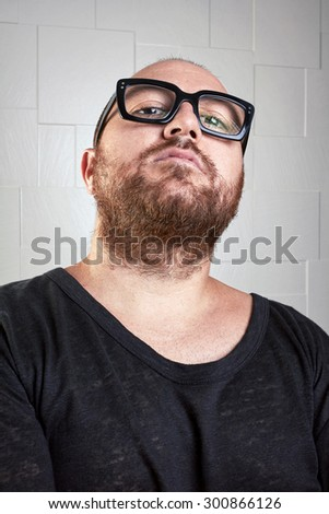 Portrait of a serious guy with a beard. Portrait of a casual dressed guy, who looks at you with superiority through his glasses. Portrait over textured background. - stock photo