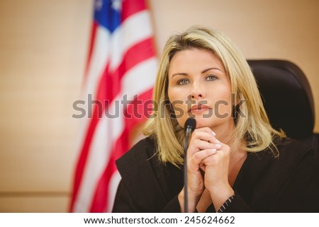 Portrait of a serious judge with american flag behind her in the court room - stock photo