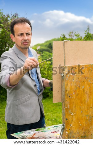 Portrait of a serious male artist in the process of painting his picture in the open air with background of beautiful trees - stock photo