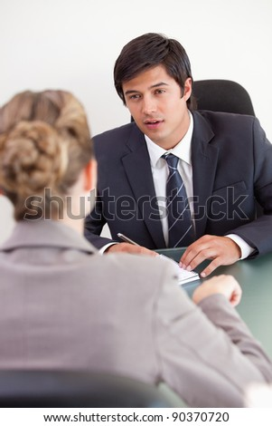 Portrait of a serious manager interviewing a female applicant in his office - stock photo