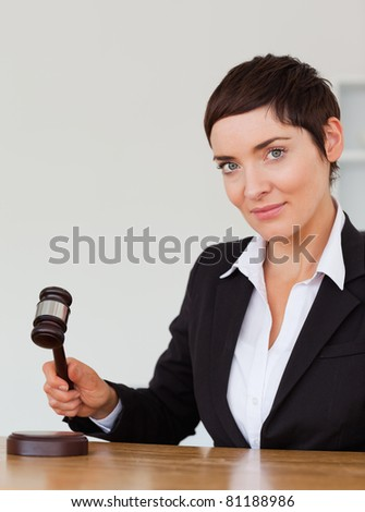 Portrait of a serious woman knocking a gavel in her office - stock photo