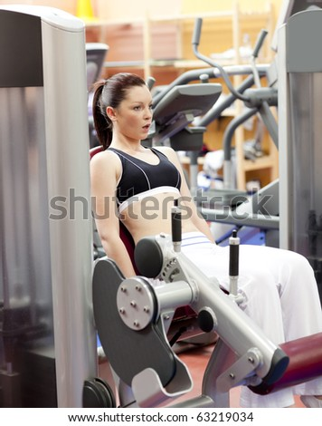 Portrait of a serious woman using a leg press in a sport centre - stock photo