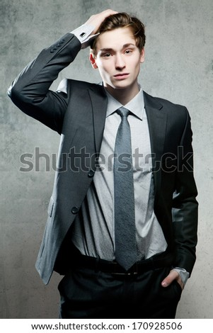 Portrait of a serious young business man, on gray background - stock photo