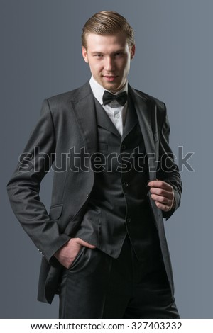 Portrait of a serious young business man, on gray background