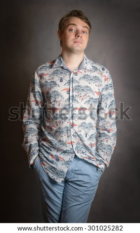 Portrait of a serious young man standing against dark background. - stock photo