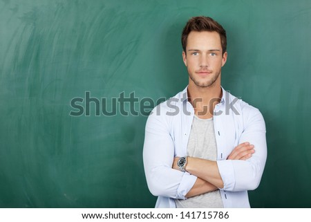 Portrait of a serious young man standing against green chalkboard - stock photo