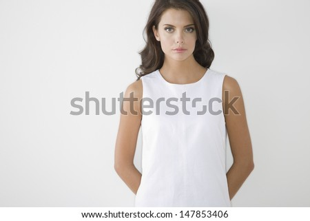 Portrait of a serious young woman in white dress against white background