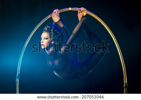 Portrait of a sexual acrobat on a dark background with a luminous gymnastic hoop. - stock photo